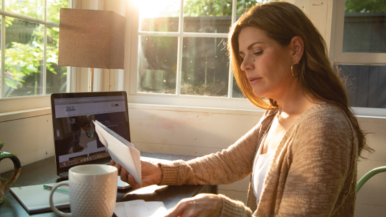 Woman drinking coffee and paying bills online