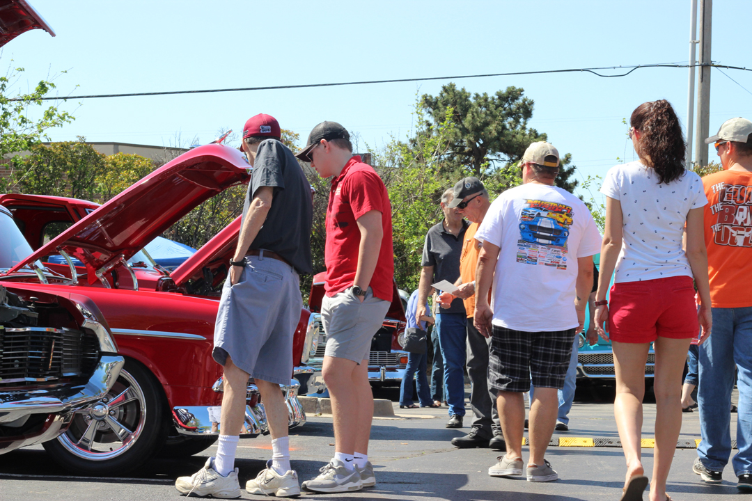 Crowds of people enjoy looking at vintage and custom cars at the 2018 Miracle Car Show held at Tinker Federal Credit Union's Operations Center.