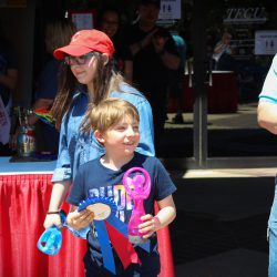 Eight year old Miracle Child Brycen hands out awards at TFCU's 2018 Miracle Car Show. His sister Harley stands behind him.