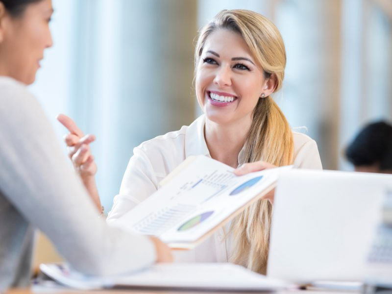 Smiling women discussing year-end financial results