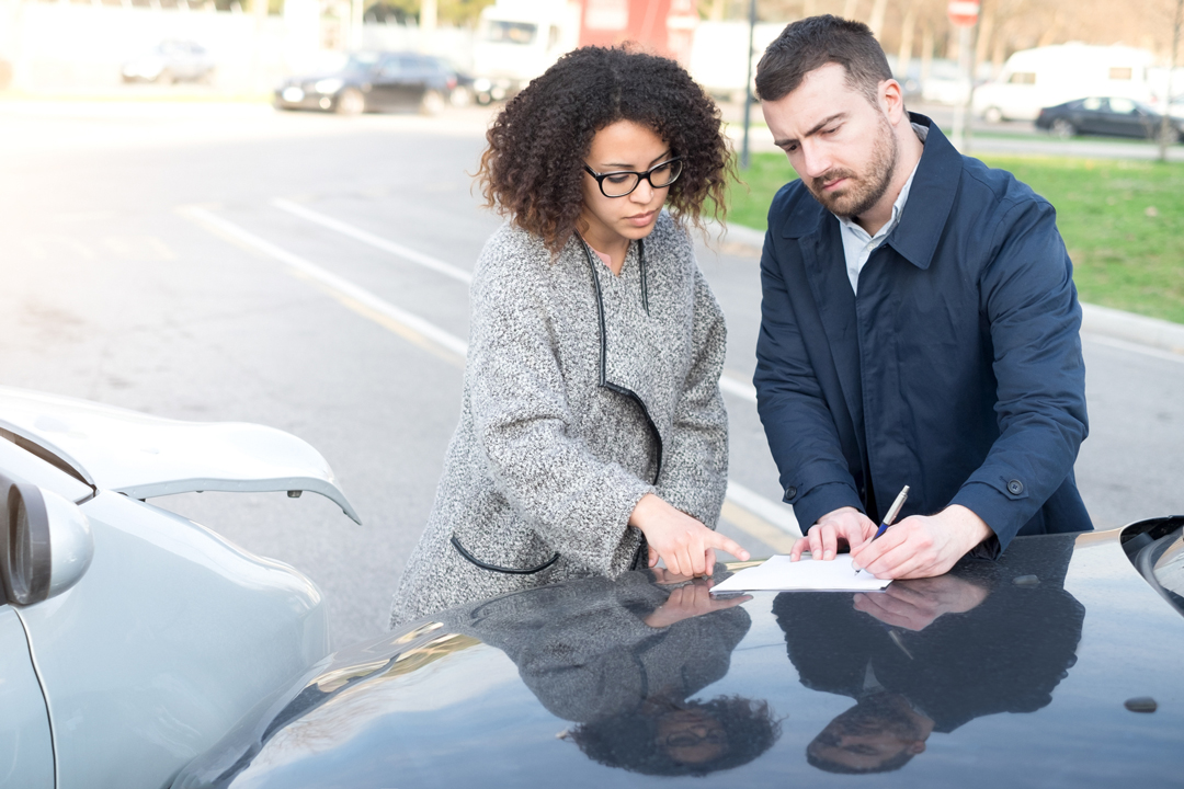 Woman and man filling out insurance forms after a vehicle accident.