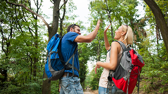 Man and woman high fiving while on walking trail.