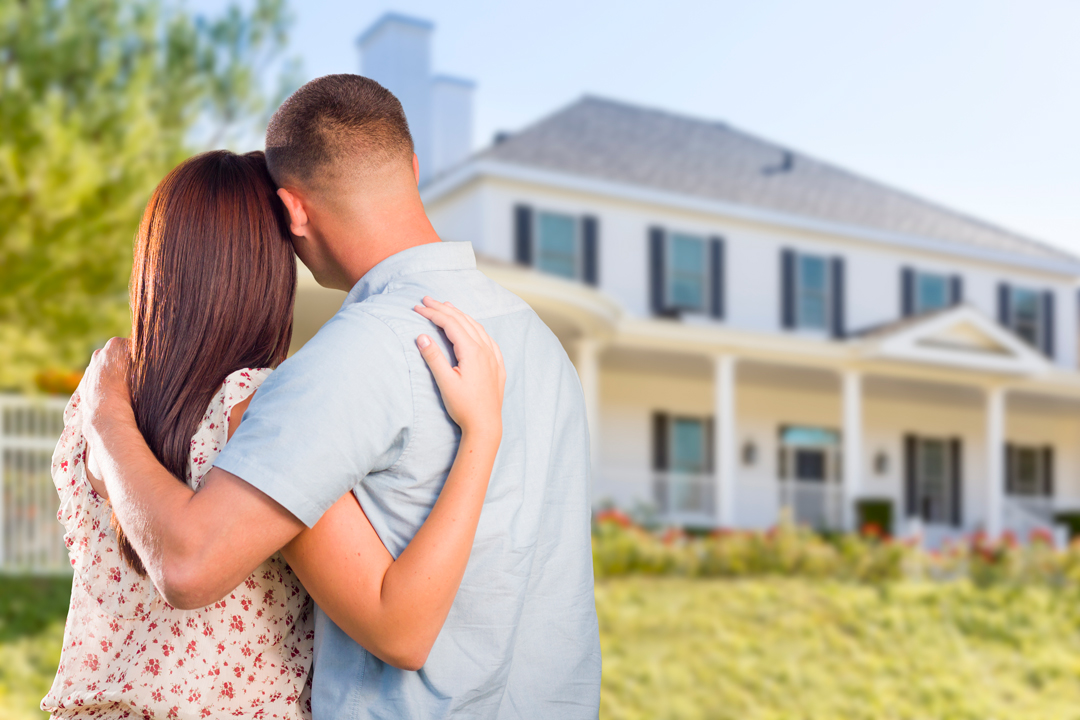 Man and woman with arms around each other looking at a new home