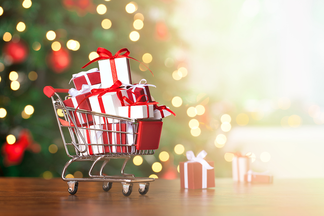 Little shopping cart full of christmas gifts with christmas tree background.