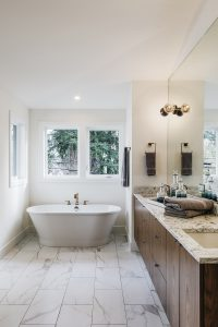 Spacious bathroom with marble floors, granite countertops and a large bathtub.