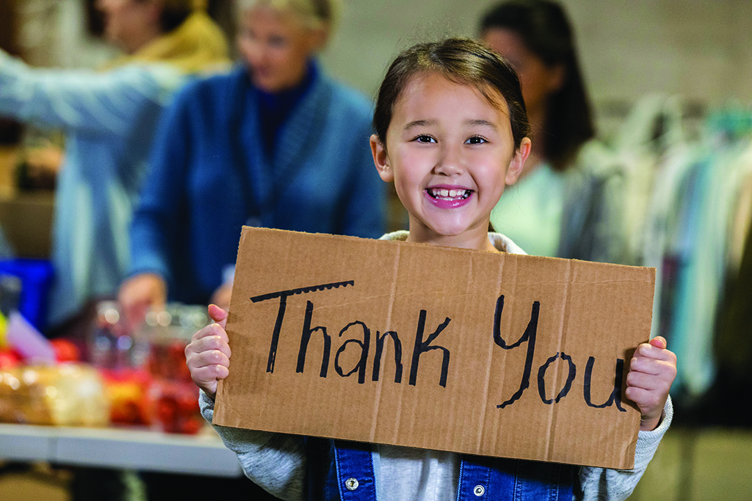 "Young girl holding a cardboard sign that says ""thank you"" and smiling with people in the background."