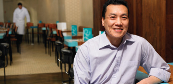 Chinese restaurant owner smiling in his dining room