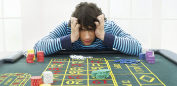 Young adult male with frustrated expression at gambling table
