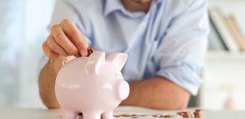 Man placing change into a piggy bank