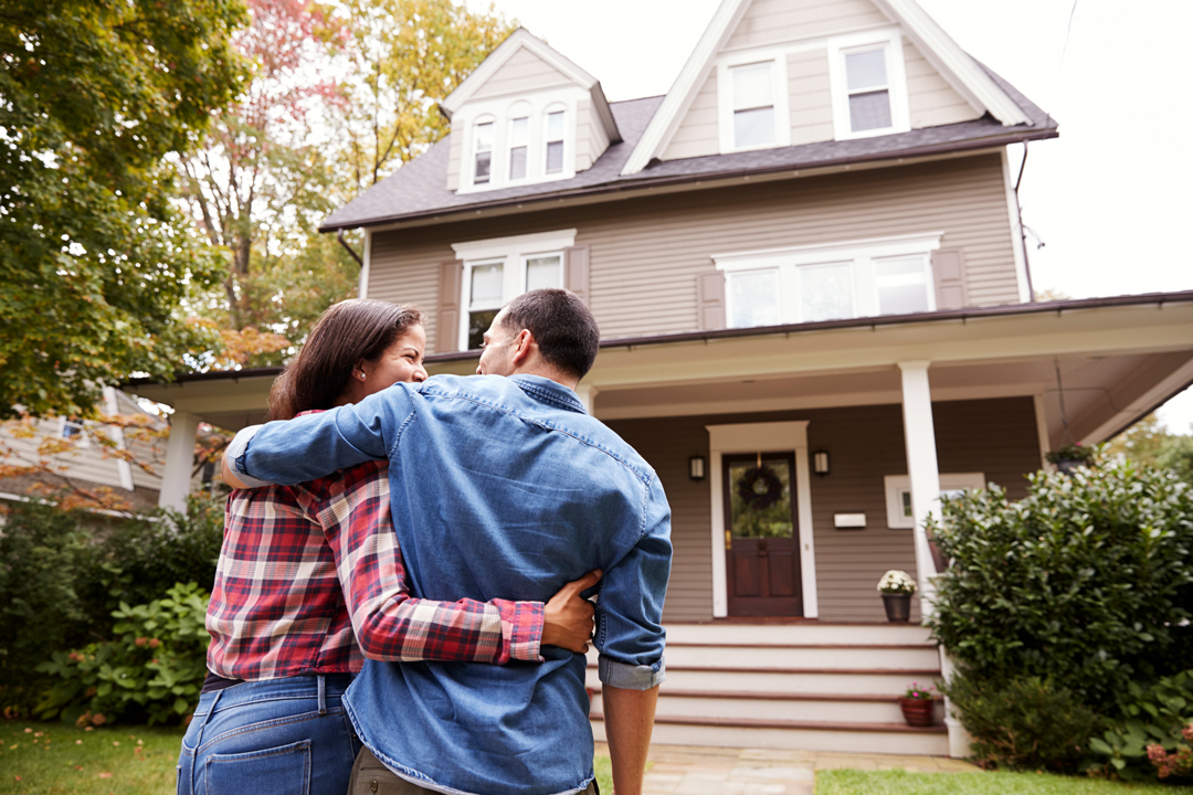Man and woman walking with their arms lovingly around each other toward a beautiful new two-story home.
