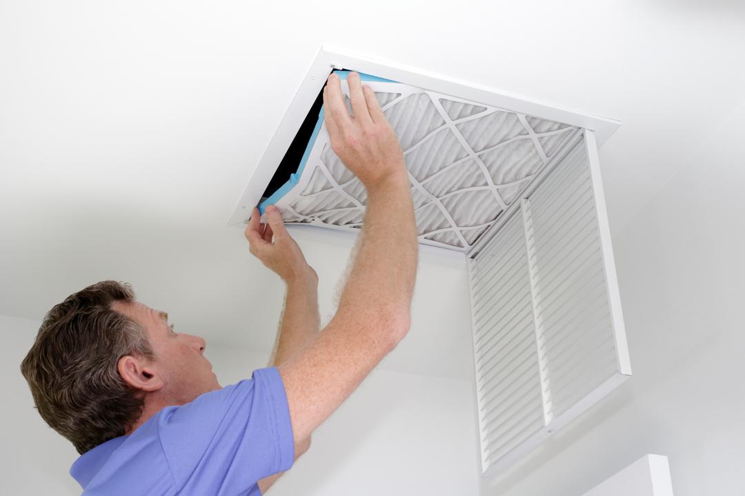 Man replacing air filter in ceiling.