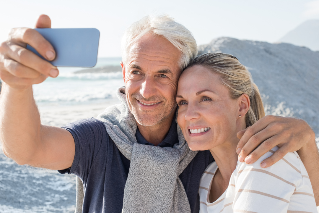 Senior man and woman taking selfie with the ocean behind them.