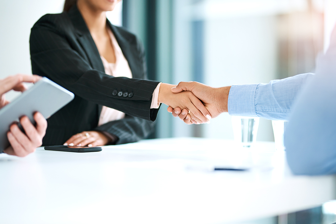 Close up shot of a business woman shaking hand with a businessman in a modern looking office.