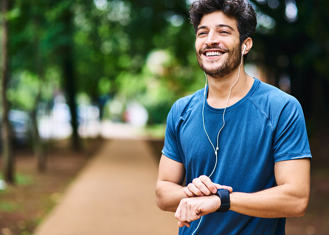 A young man checking his watch while exercising outdoors with earbuds in.
