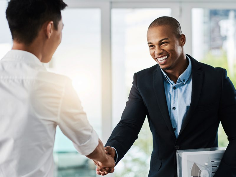 Shot oTwo young businessmen shaking hands in a modern office
