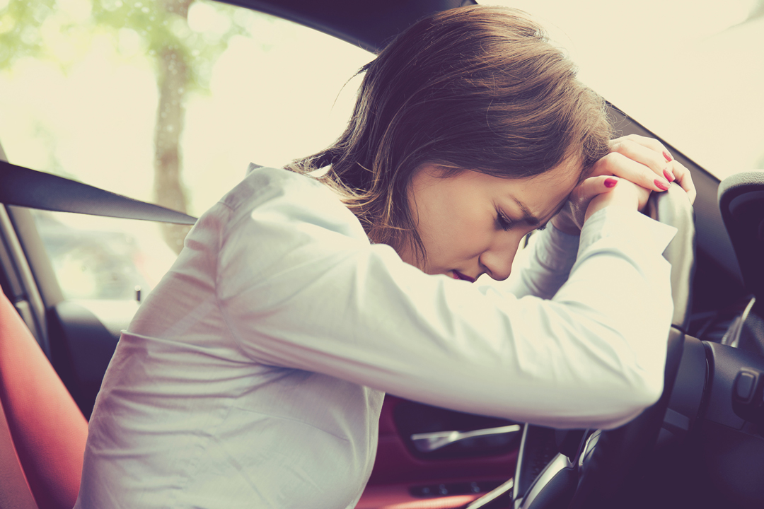 Stressed woman sitting in driver seat of vehicle with head and hands resting on steering wheel.