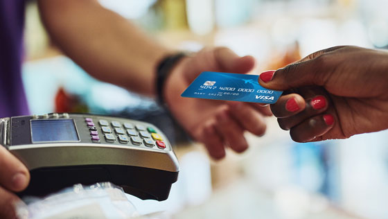 Close up of member making a store purchas with a TFCU Visa Classic credit card