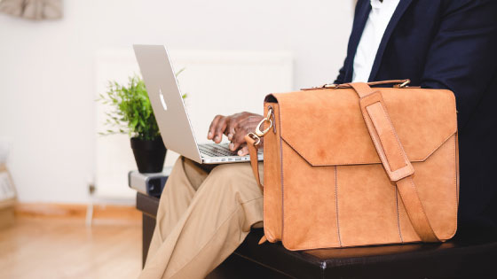 Close up of man wearing suit on laptop with briefcase