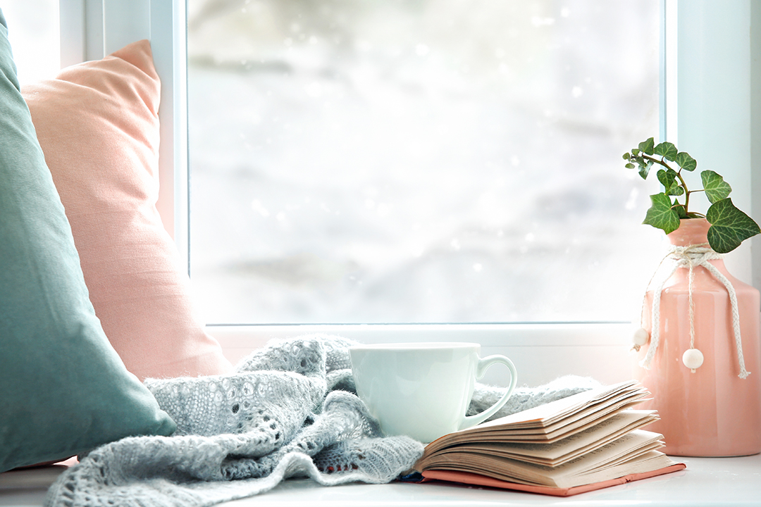 A mug, blanket,book, and pillows in front of a window with a snowy background