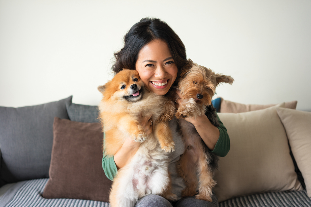 Smiling woman sitting on couch, cuddling two small dogs