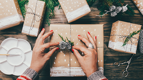 Close up of woman wrapping gifts with brown paper, twine, pine cones and greenery.