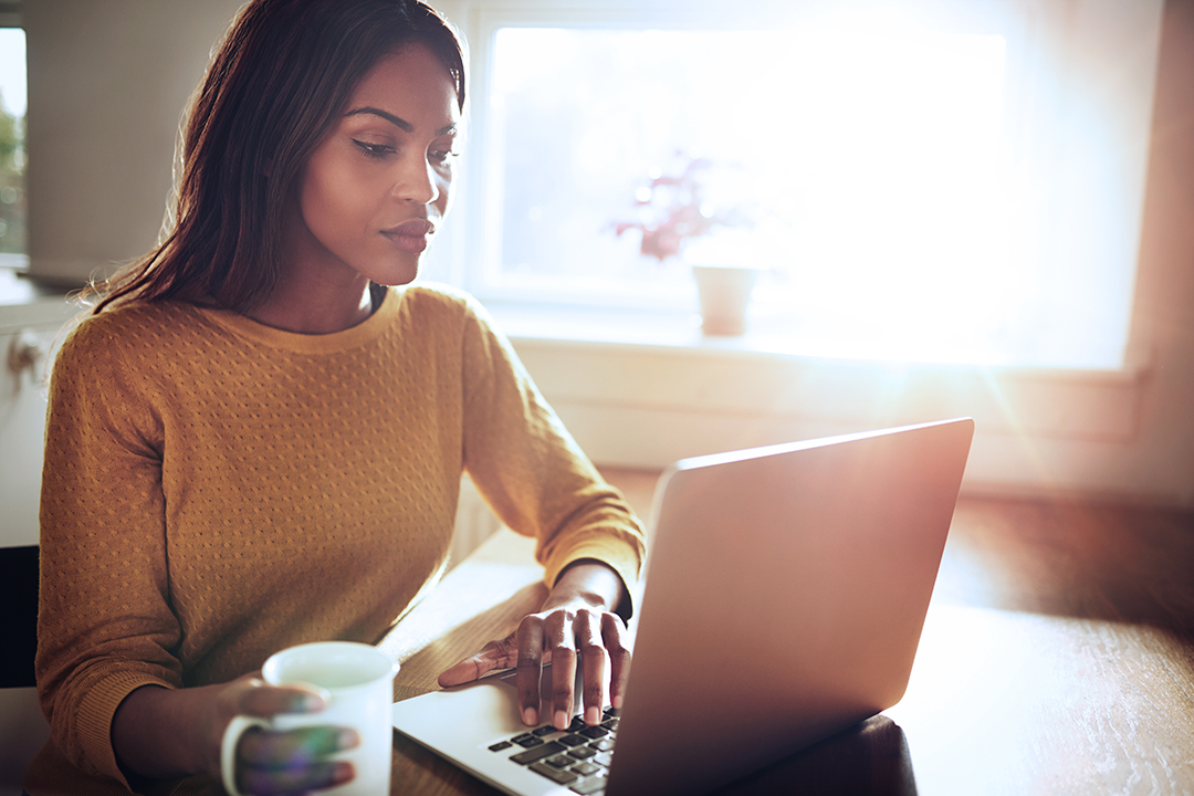 Young woman on her laptop with a mug
