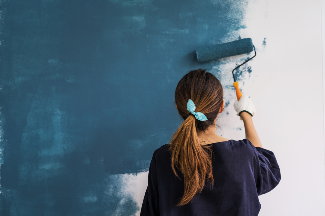 Young woman with hair in pony tail painting a wall blue.