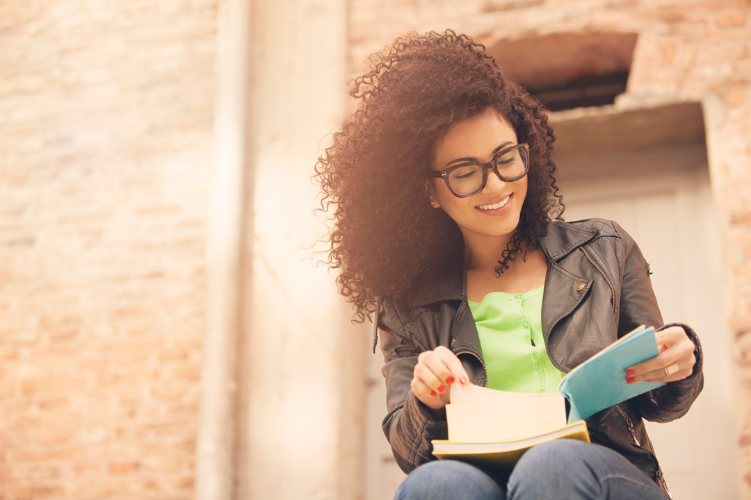 Young, happy woman in glasses looking at a book on her lap.