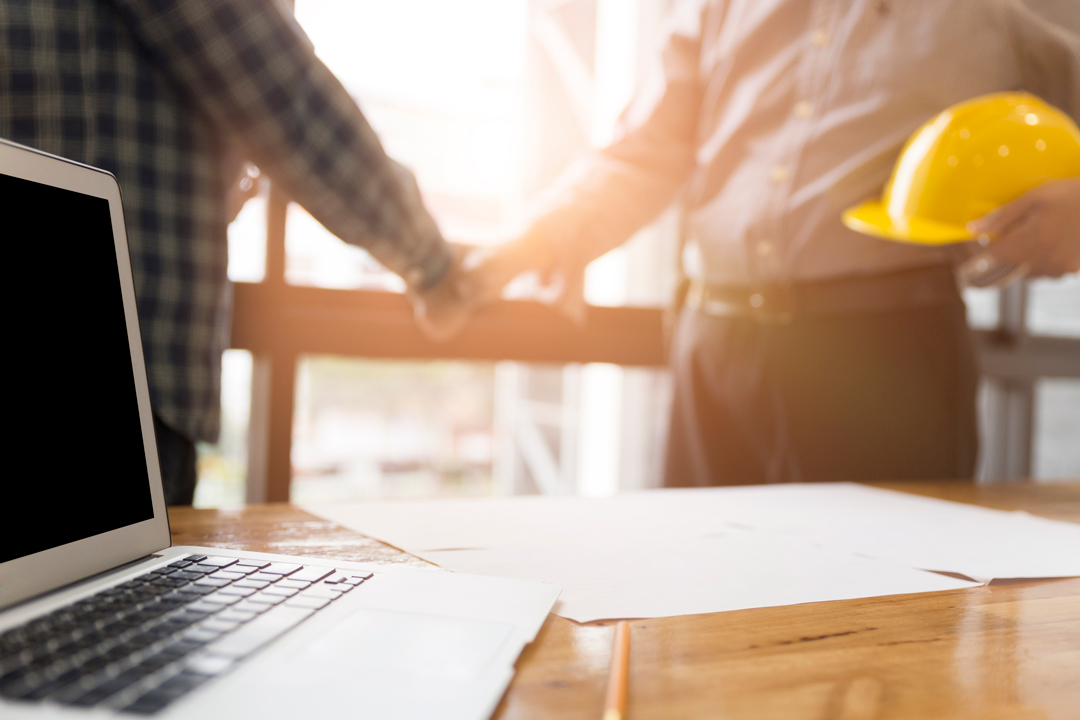 Home owner shaking hands with a building contractor