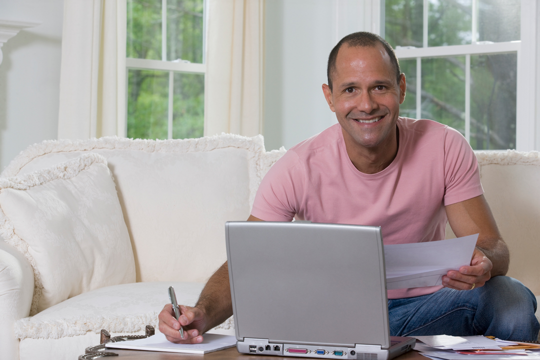 Man in pink t-shirt sitting on white couch and sorting out bills in front of a laptop