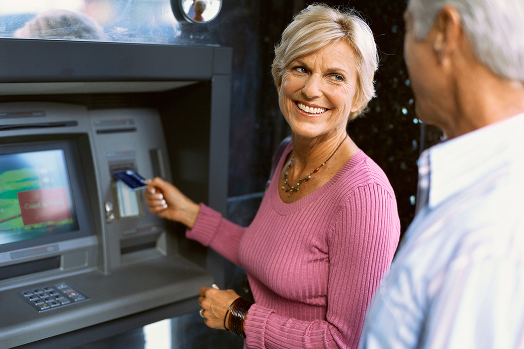 Older woman using ATM while smiling at husband